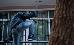 Ladrón armado intentando entrar a una casa por la ventana